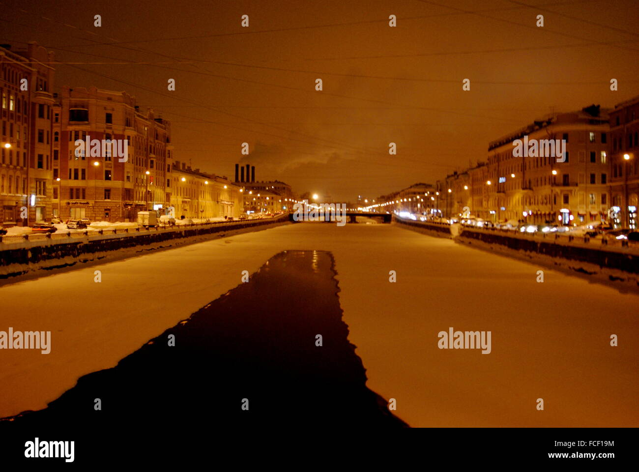Frozen Canal Surrounded By Illuminated Buildings At Night - Stock Image