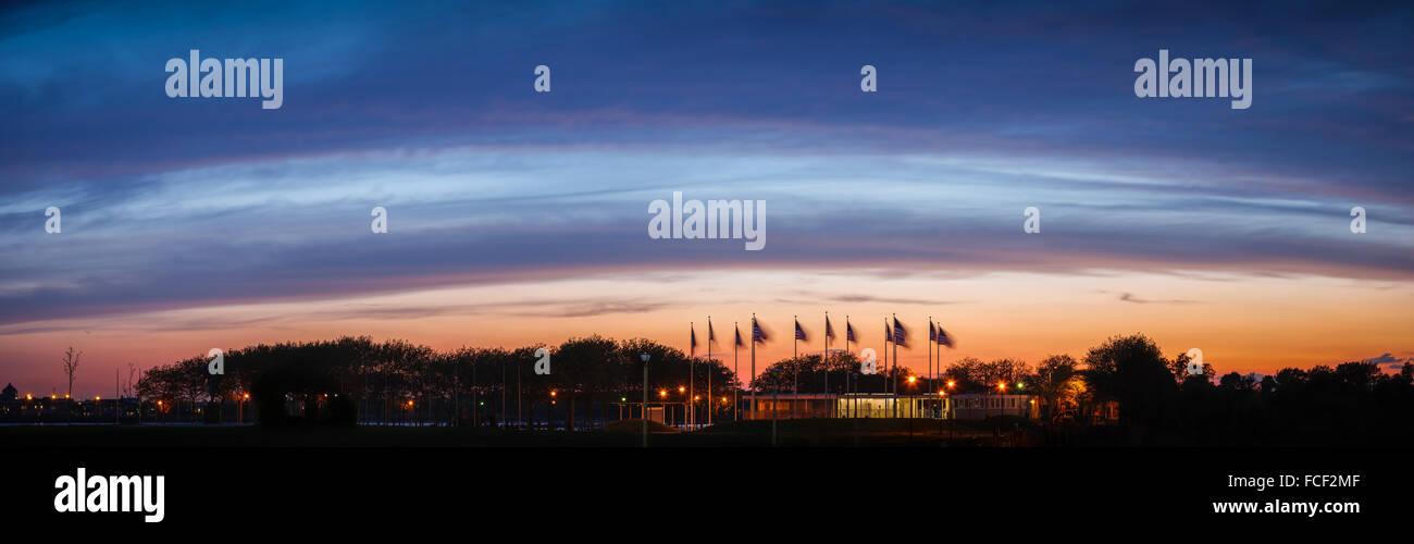 Flag Plaza's American banners flapping in the wind against a background of deep blue clouds at sunset near Jersey - Stock Image