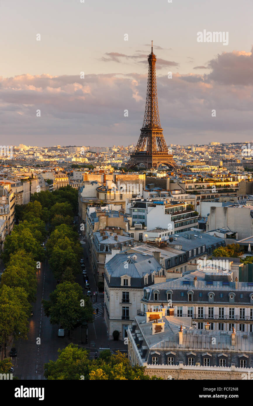 Avenue Iena and Eiffel Tower lit by a summer sunset light. Elevated view of 16th arrondissement rooftops in the - Stock Image