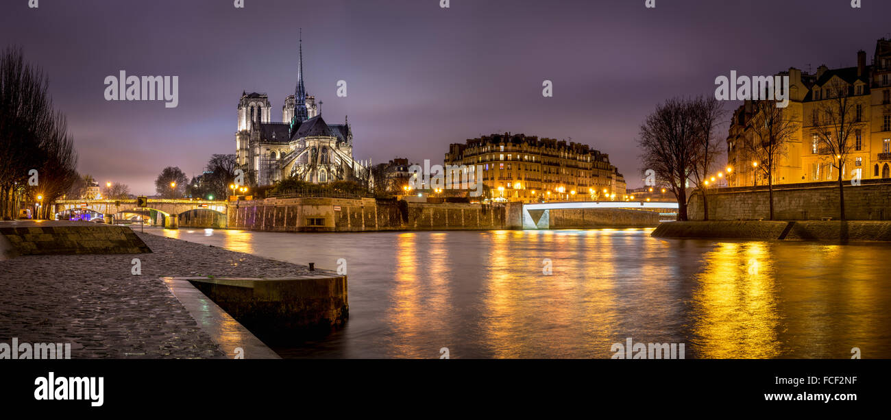 Evening panoramic of Notre Dame de Paris Cathedral on Ile de La Cite with city lights reflecting on the Seine River. - Stock Image