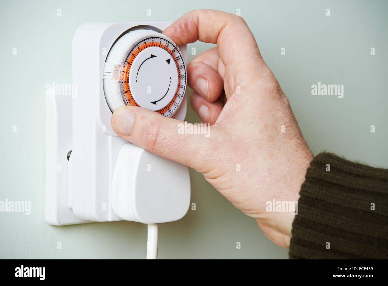 Man Adjusting Timer On Electrical Socket - Stock Image