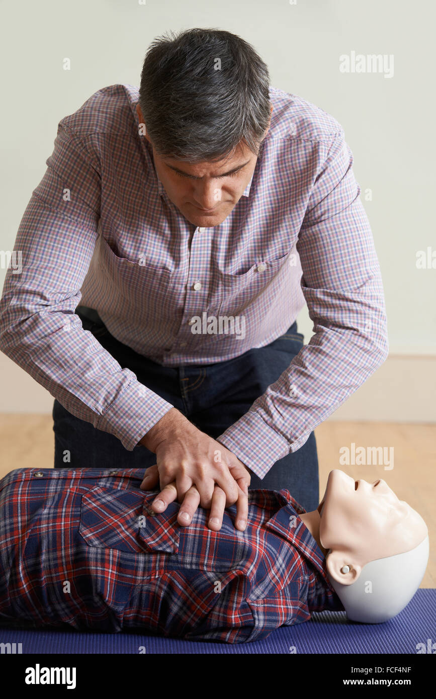 Man Using CPR Technique On Dummy In First Aid Class - Stock Image