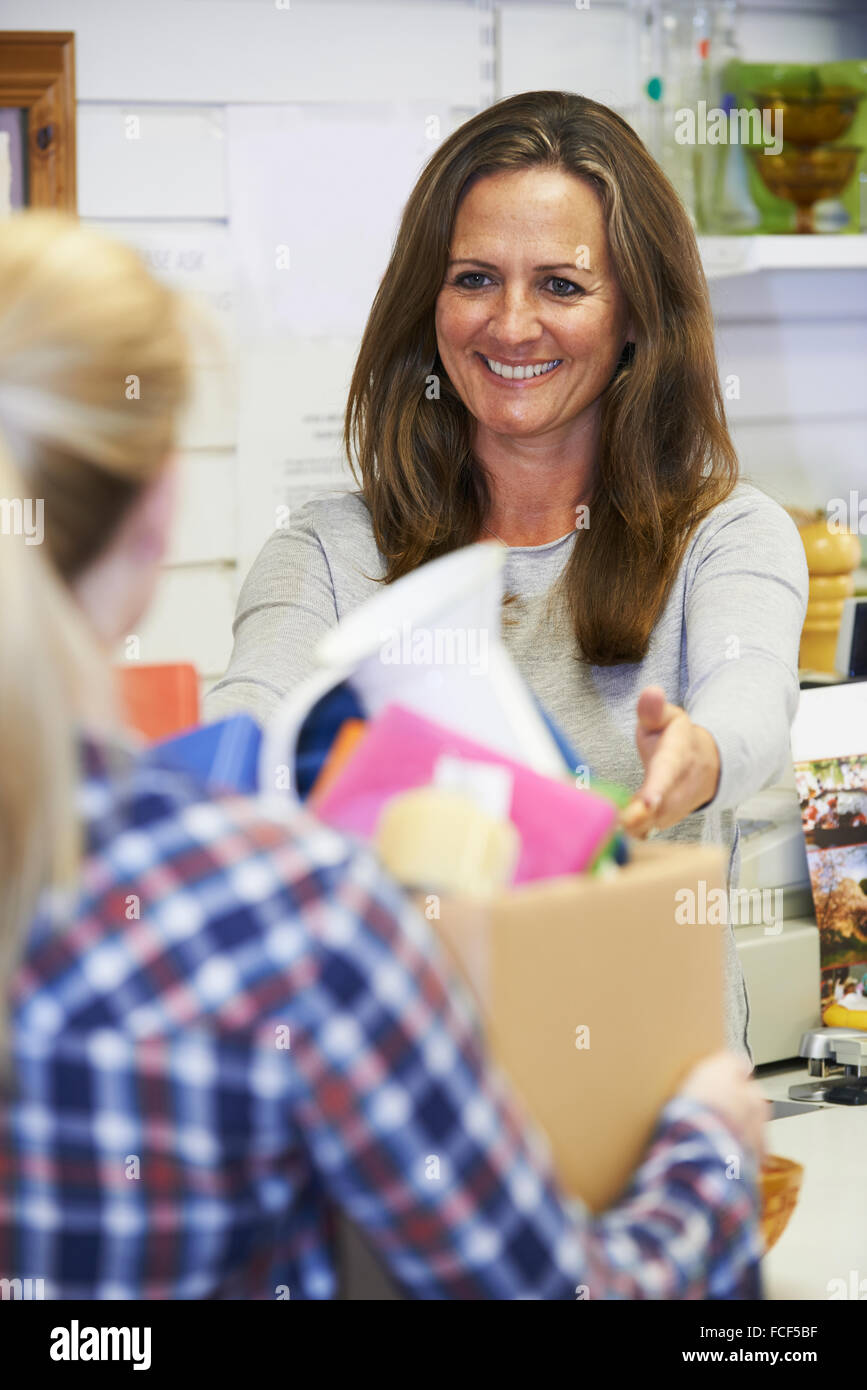 Woman Donating Unwanted Items To Charity Shop - Stock Image