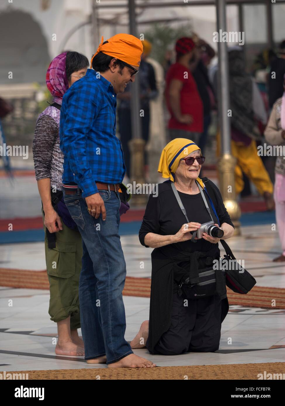Western visitors interact with Indians in New Delhi, India - Stock Image