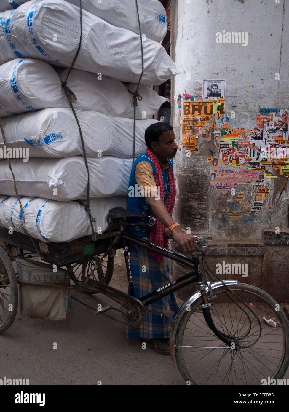 Man pulling overloaded cycle cart, Varanasi, Uttar Pradesh, India. - Stock Image