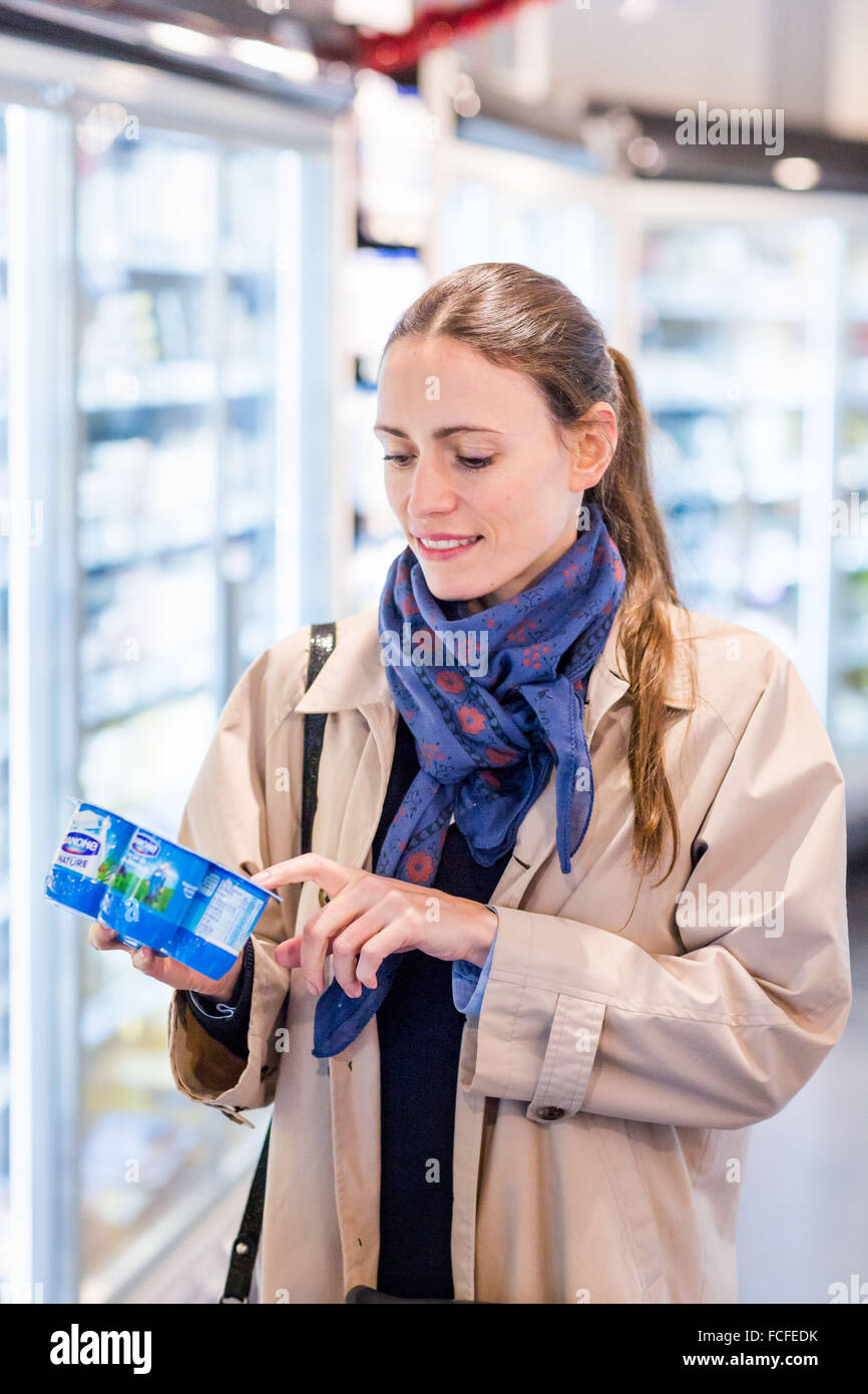 Woman shopping for dairy products in organic supermarket. - Stock Image