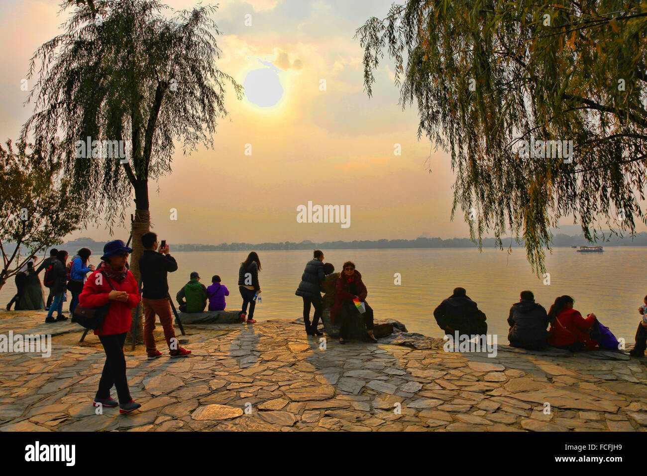 Chinese People watching sunset at Summer place of Empress Dowager near Beijing; China - Stock Image