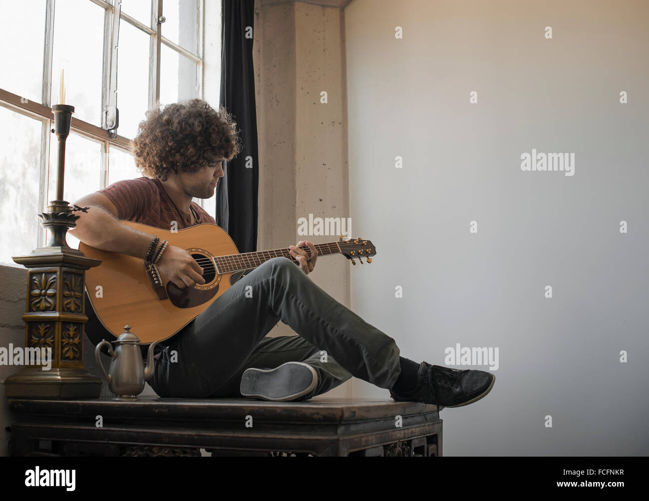 Loft living. A young man playing guitar sitting by a window. - Stock Image