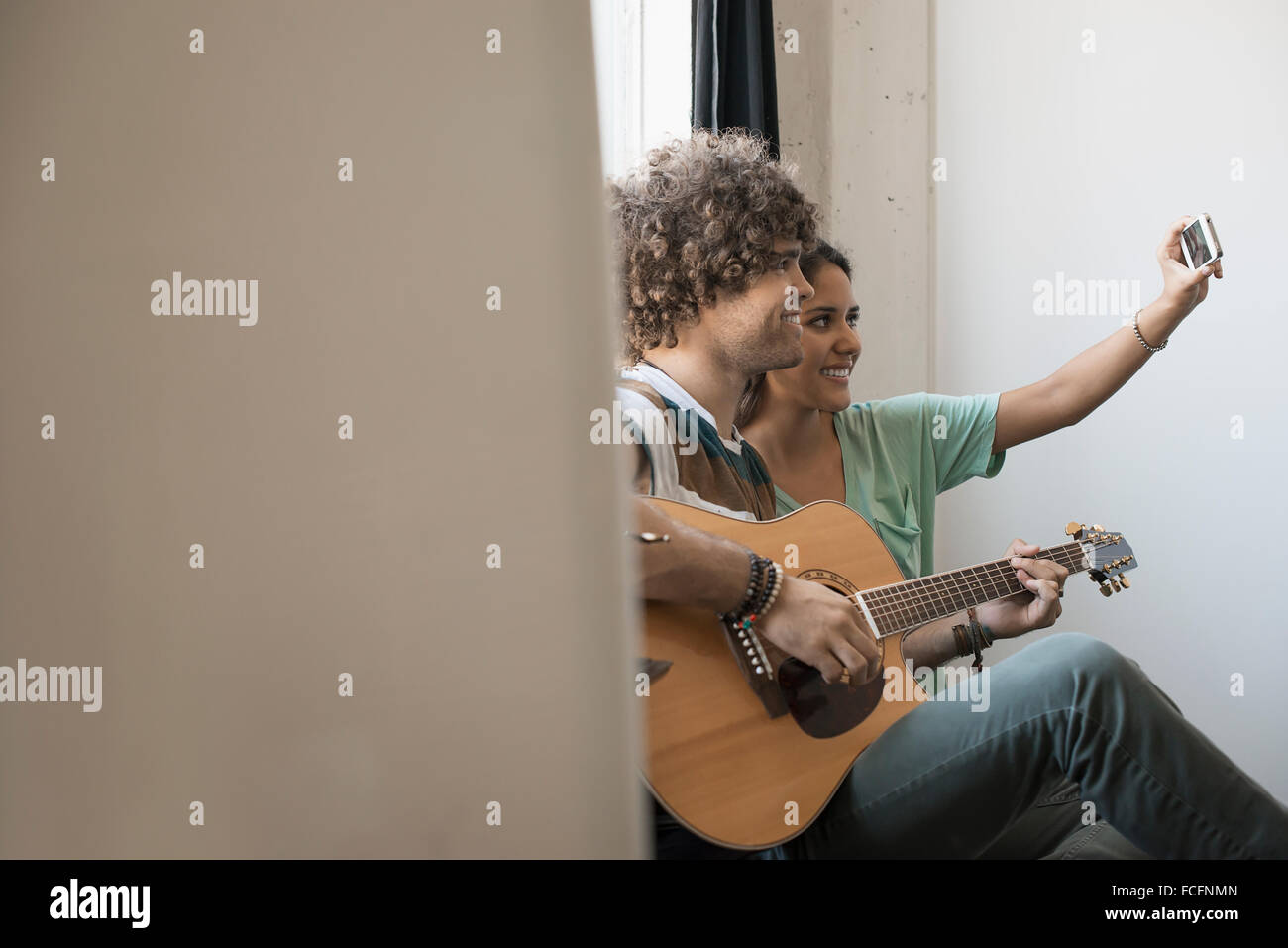 Loft living. A young man playing guitar and a woman beside him taking a selfy with a smart phone. - Stock Image