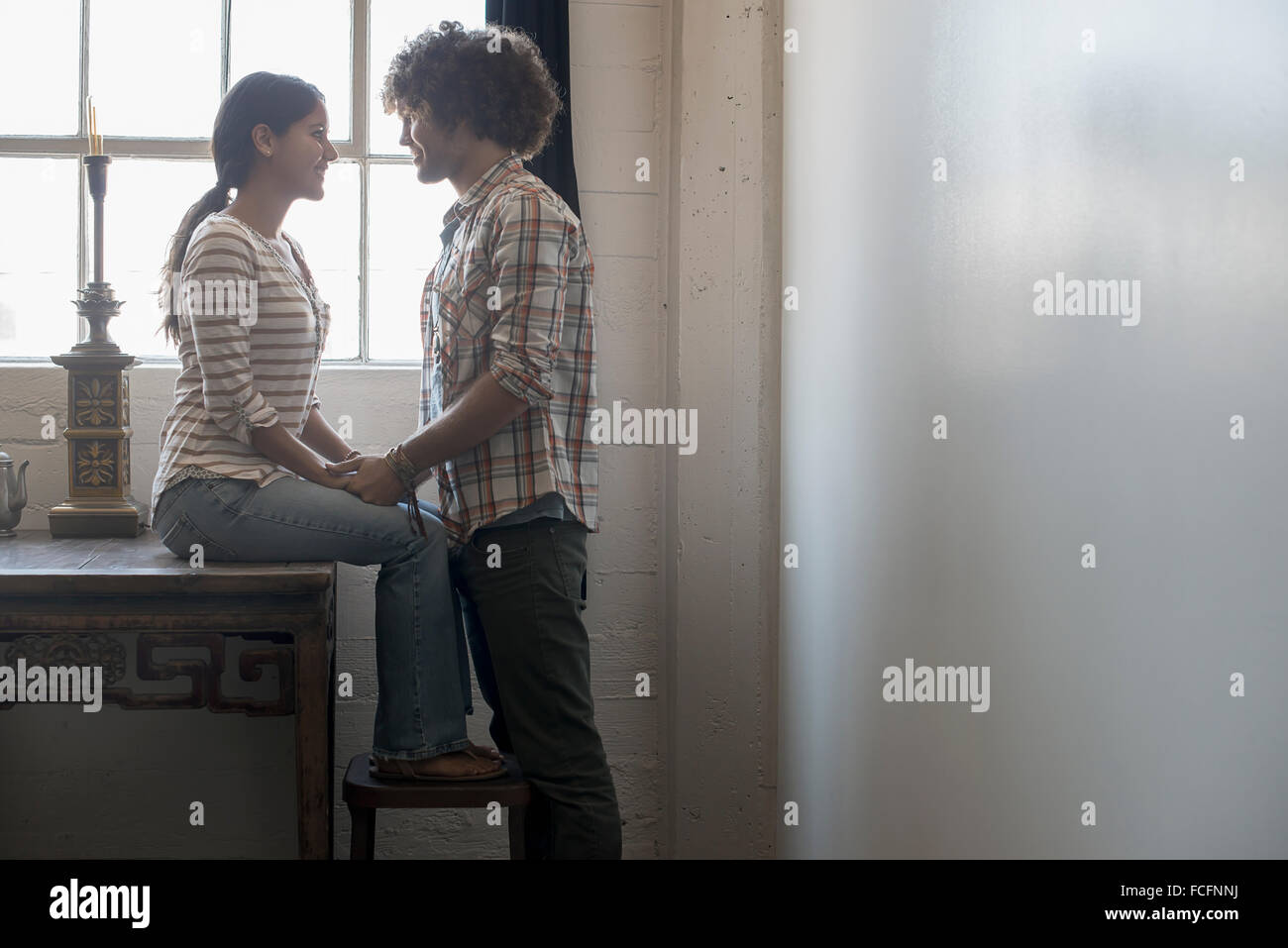 Loft living. A couple facing each other holding hands. - Stock Image