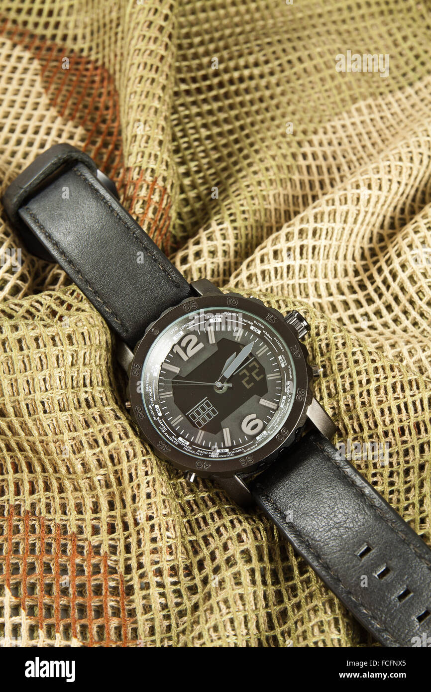Men's Watch Chronograph on camouflage netting - Stock Image