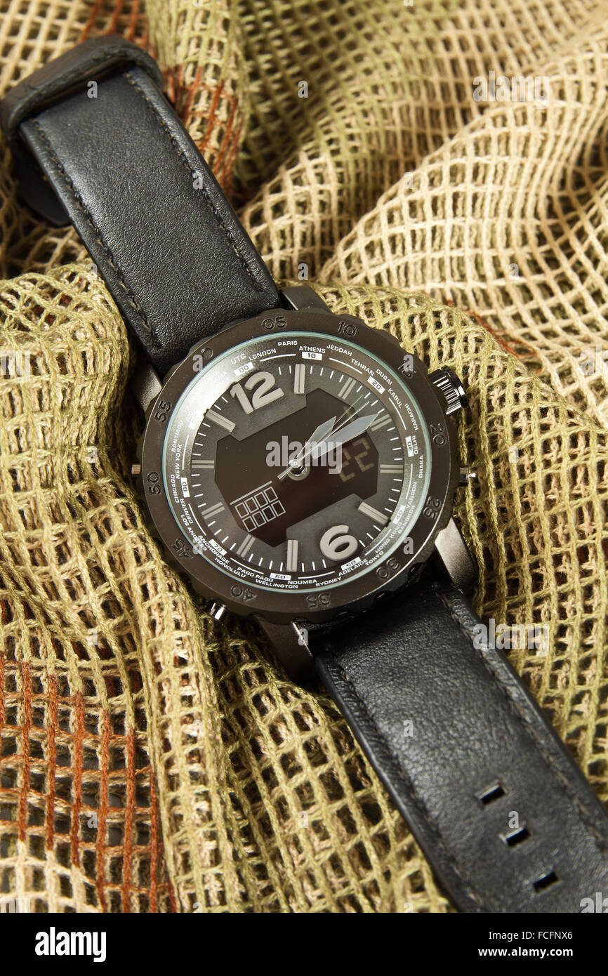 Men's Watch Chronograph on camouflage netting Stock Photo