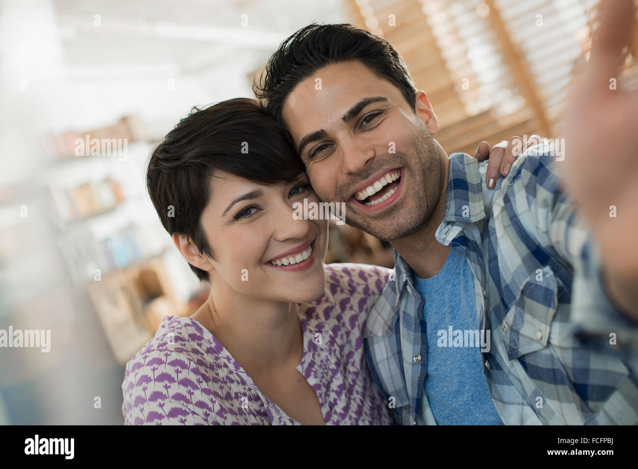 A couple, man and woman posing for a selfy. - Stock Image