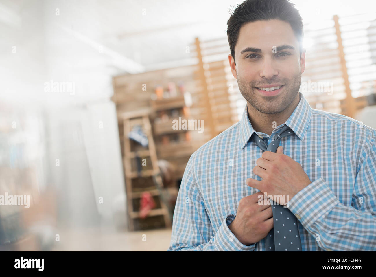 A man adjusting his tie looking at the camera. - Stock Image