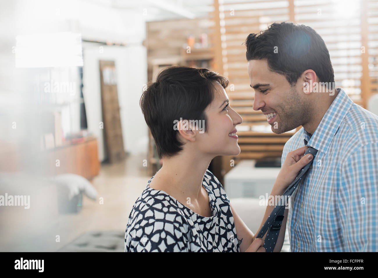 A woman adjusting a man's tie, smiling at him. - Stock Image