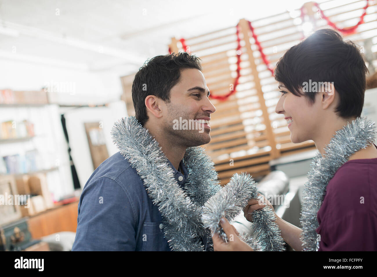 A room decorated with tinsel and streamers. A man and woman wearing silver tinsel around their necks. - Stock Image