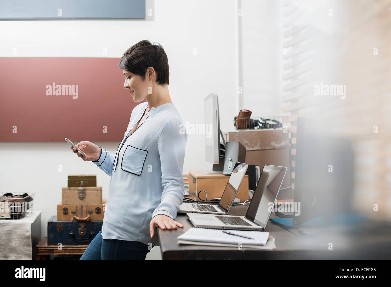 A woman in a home office with a desk with two laptops, checking her smart phone. - Stock Image