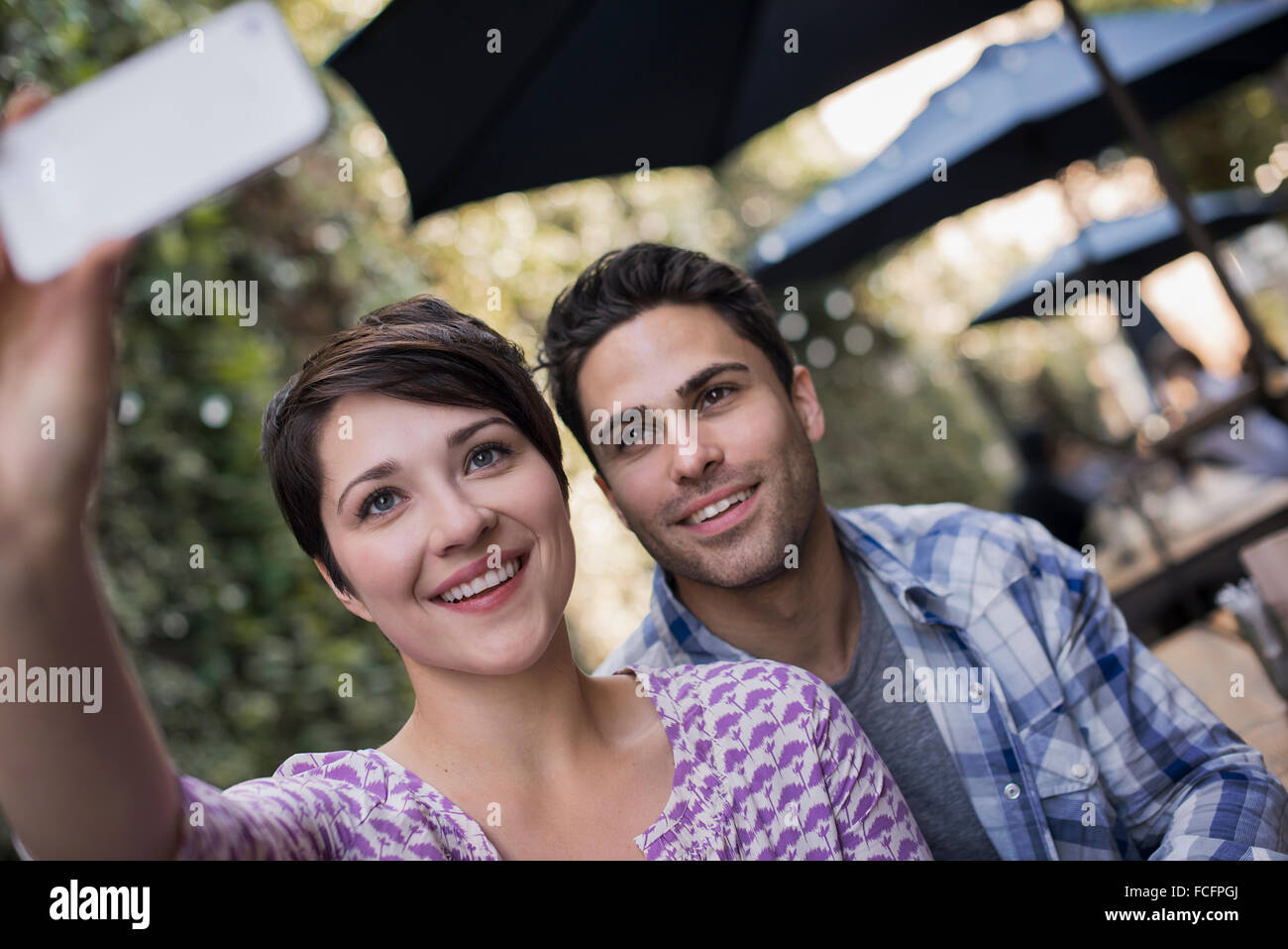 A couple seated at an outdoor city cafe, taking a selfy with a smart phone. - Stock Image
