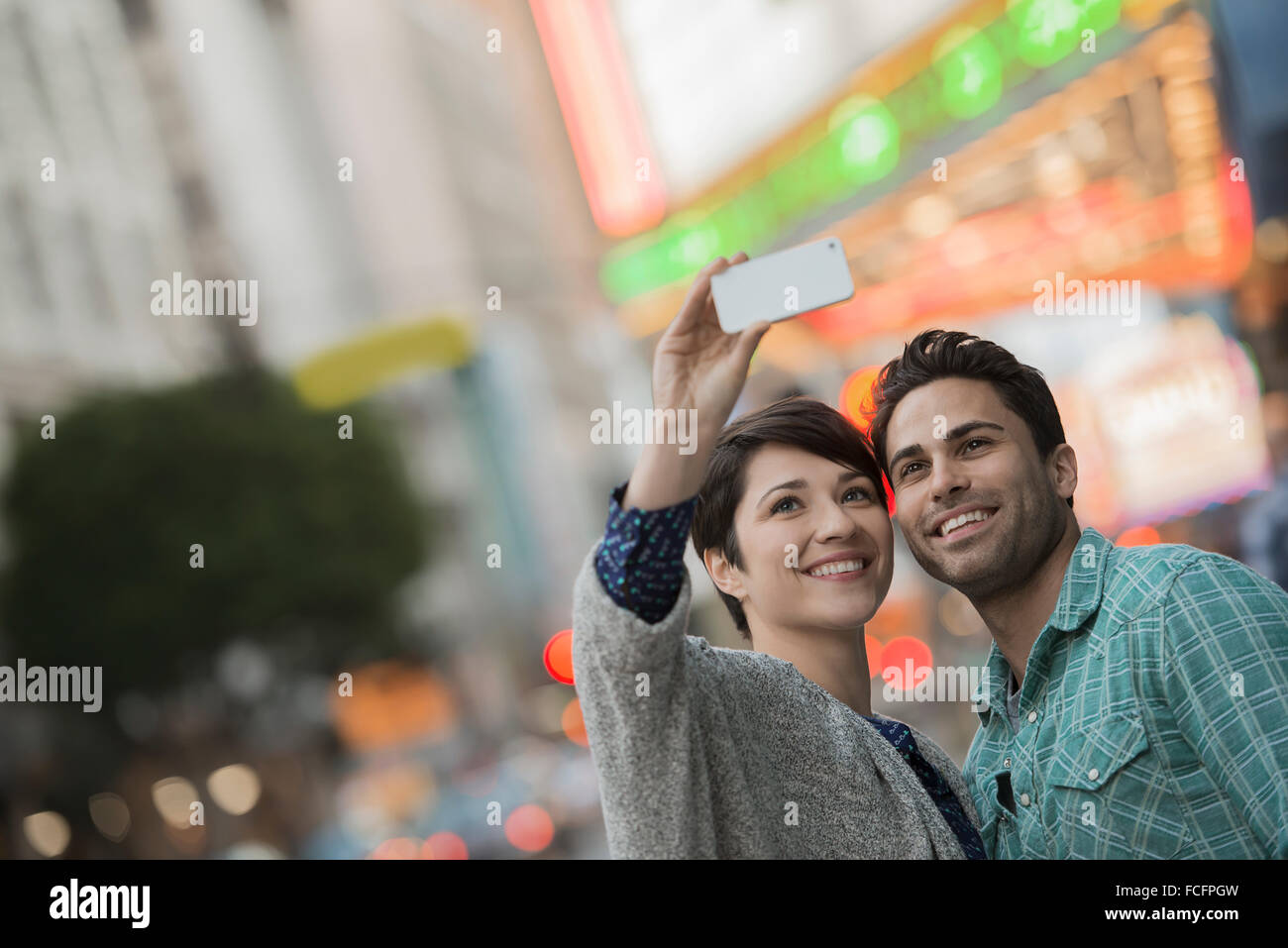 A couple, man and woman on a city street taking a selfy with a smart phone. - Stock Image