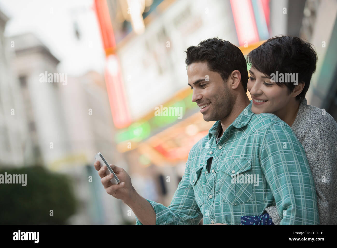 A couple, man and woman hugging on a city street. Man holding a smart phone. - Stock Image