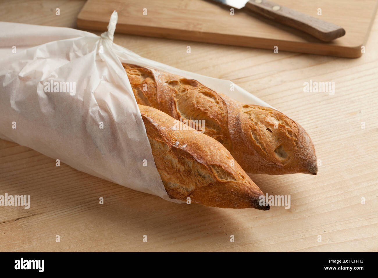 Traditional fresh french baguettes packed in paper - Stock Image