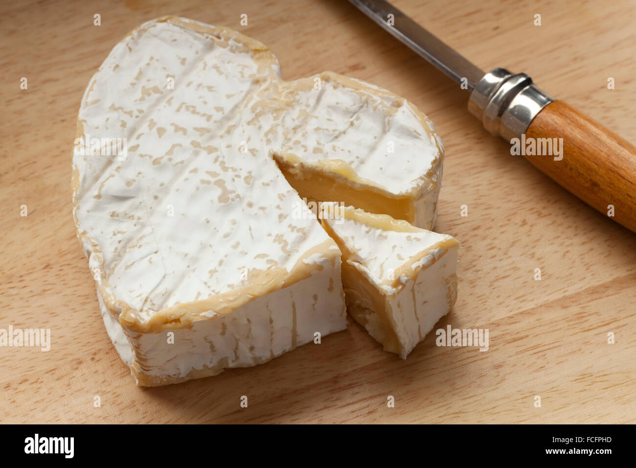 Traditional French neuchatel ripe cheese and a slice - Stock Image