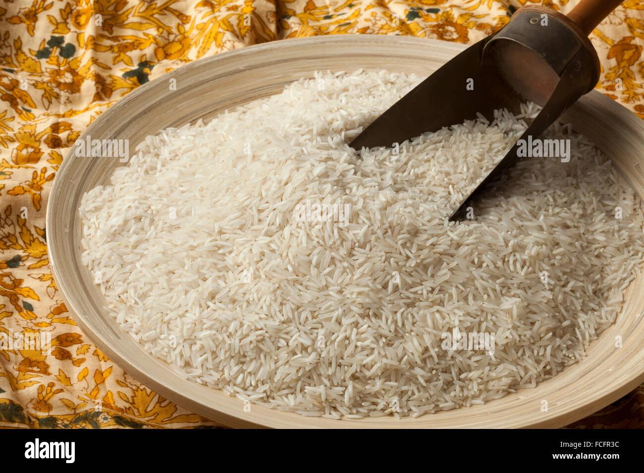 Bowl and shovel with raw Basmati rice - Stock Image