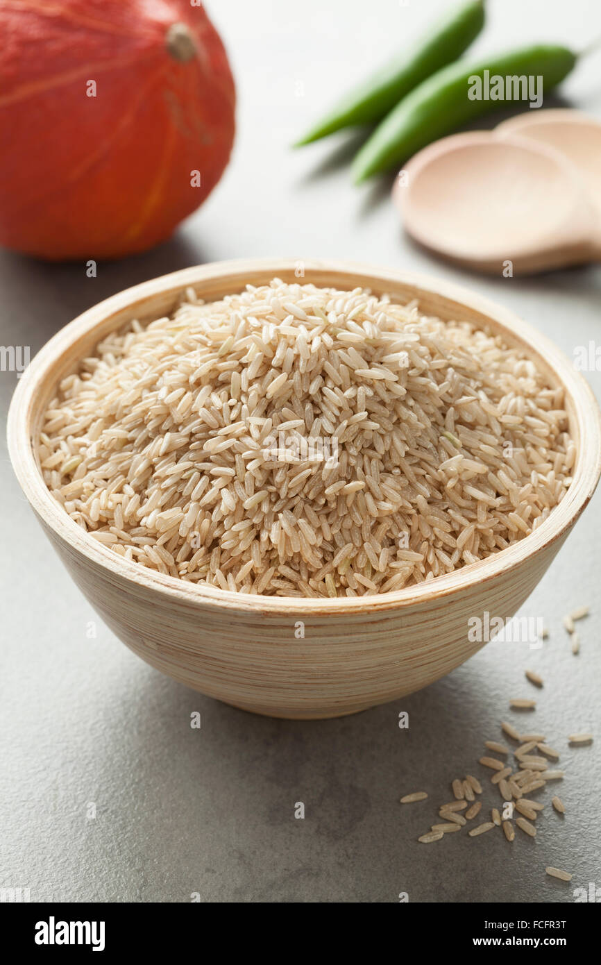 Raw brown rice in a bowl - Stock Image