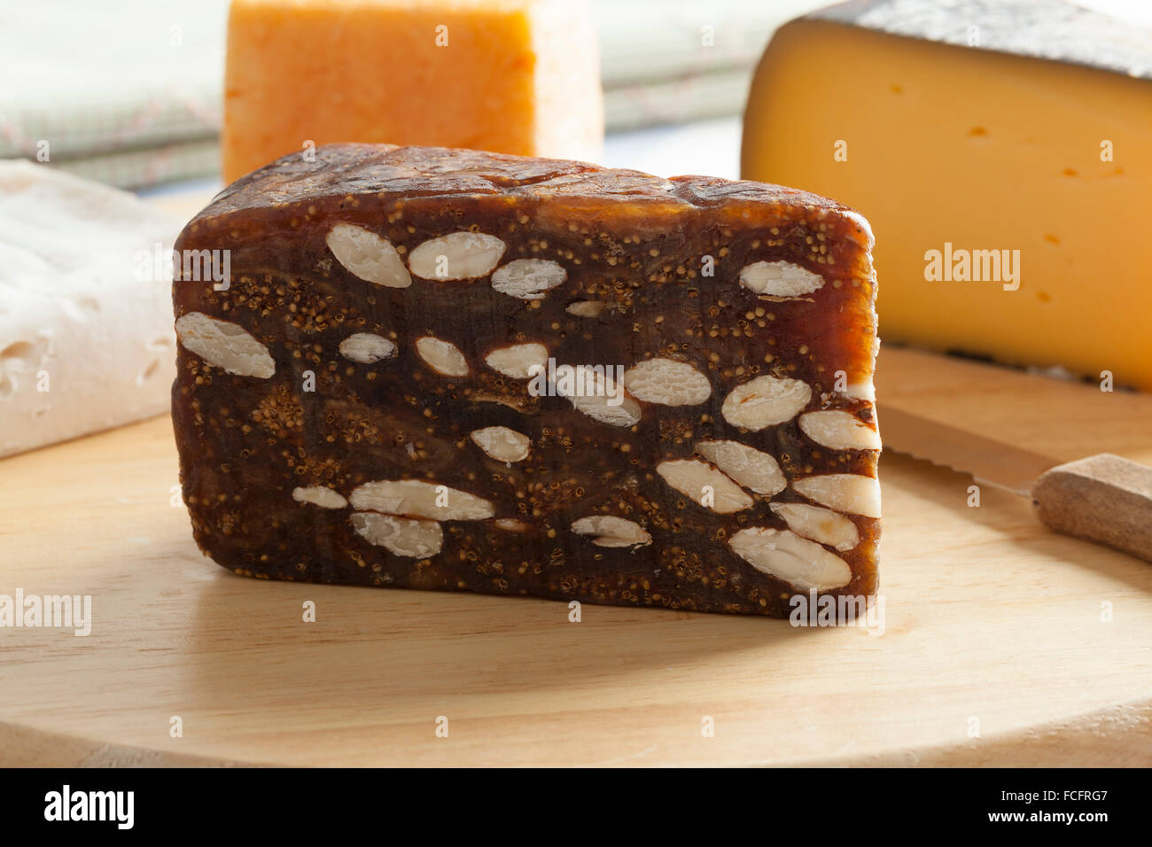 Piece of fig bread on a cheese board - Stock Image