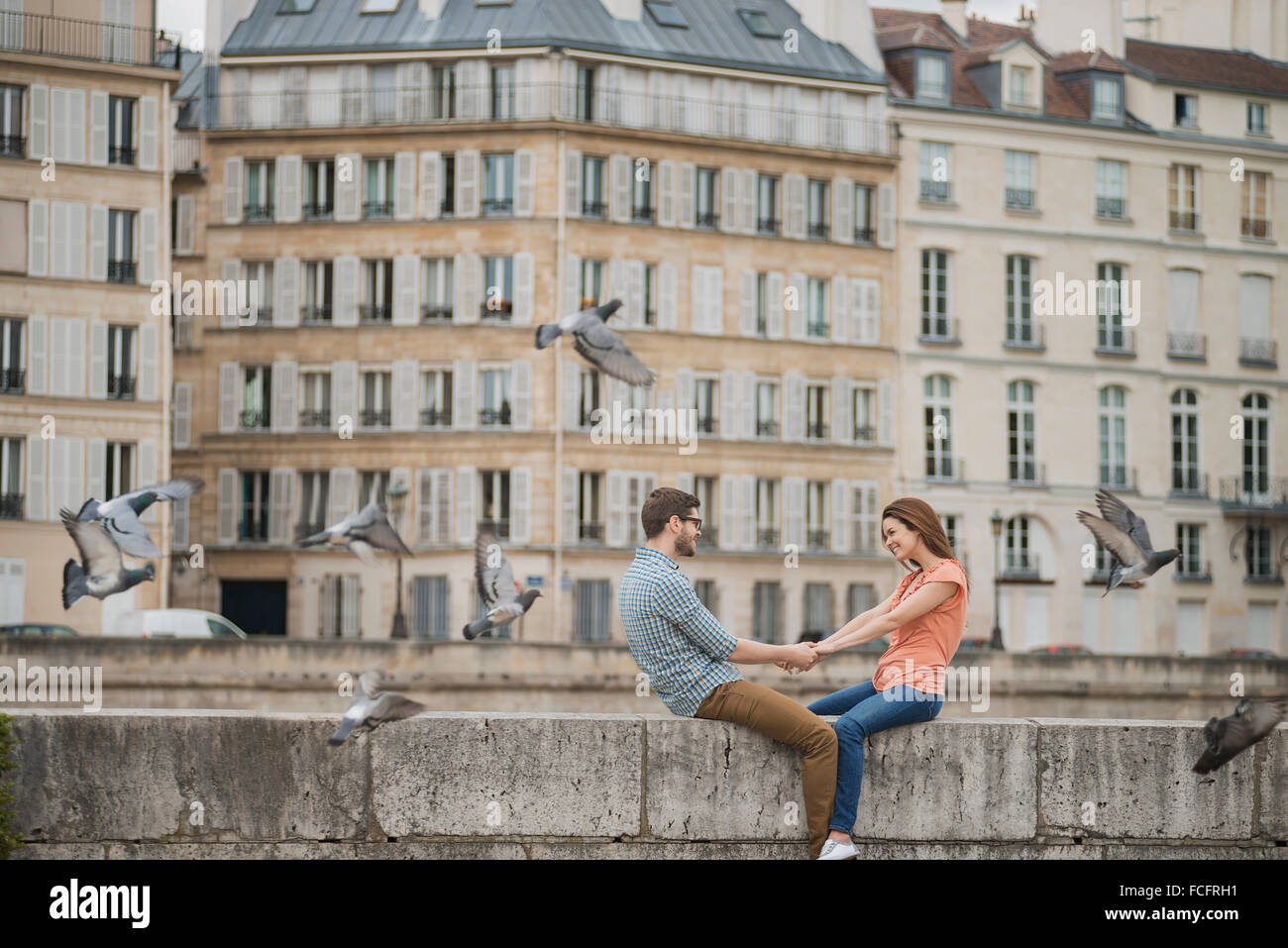 A couple, man and woman sitting on the parapet of a bridge over the River Seine. - Stock Image