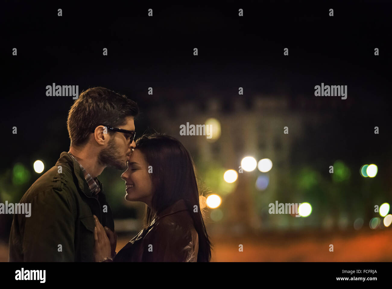 A couple kissing in a city at night. - Stock Image