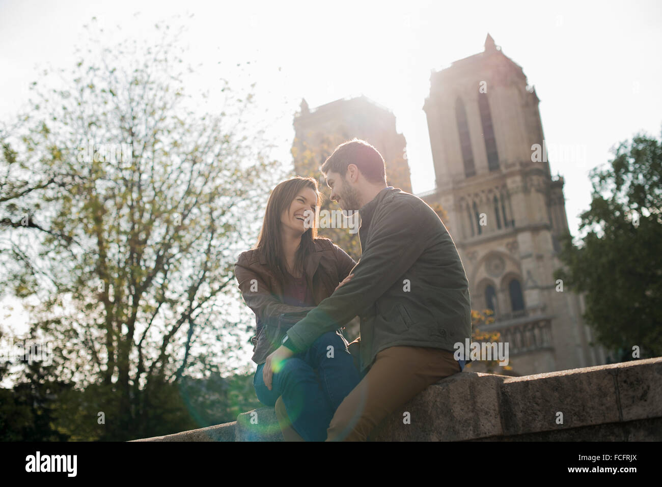 A couple in a romantic mood, side by side with arms around each other outside Notre Dame Cathedral in Paris. - Stock Image