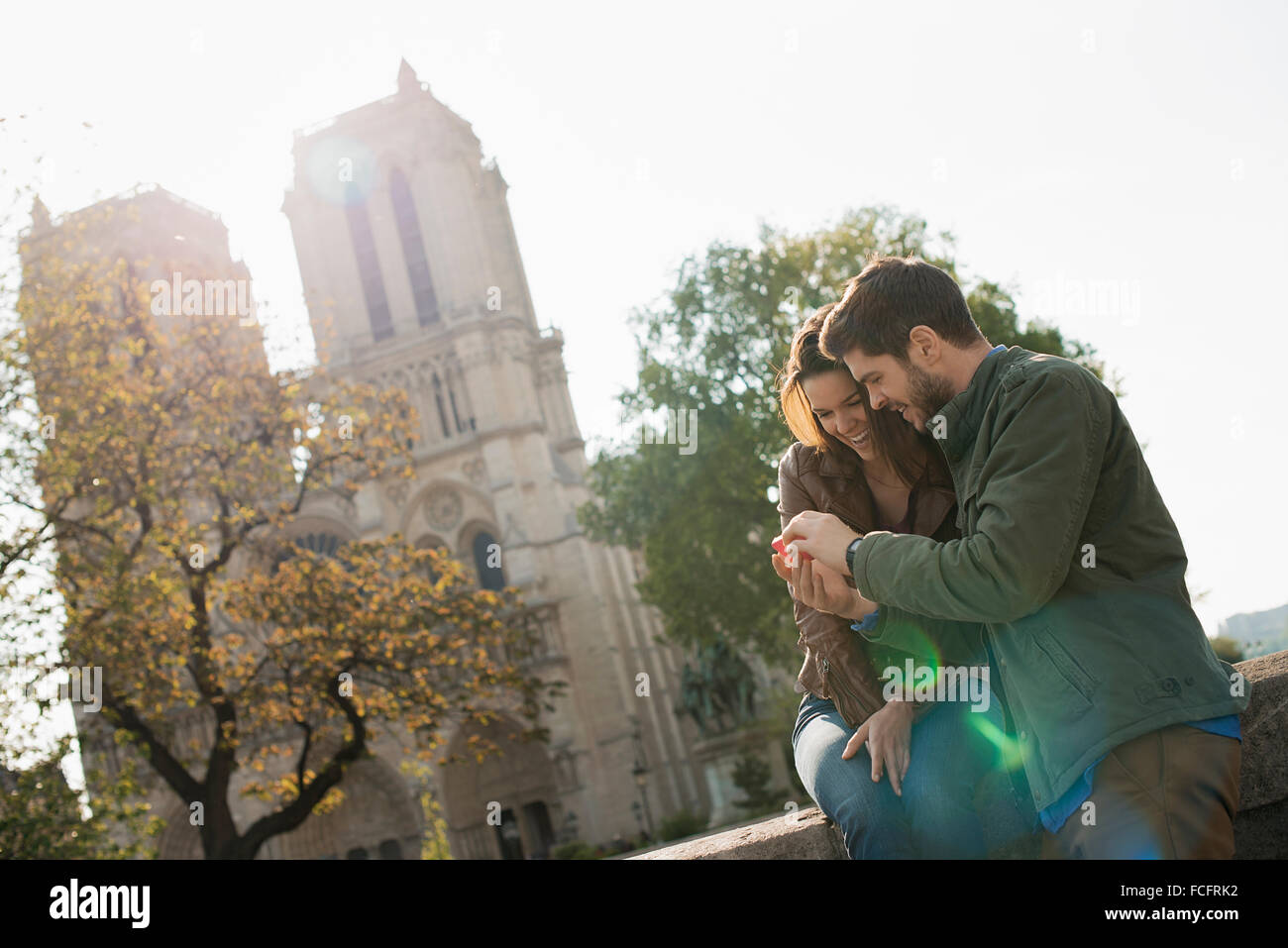 A couple side by side looking a a smart phone screen outside Notre Dame cathedral in Paris. Stock Photo