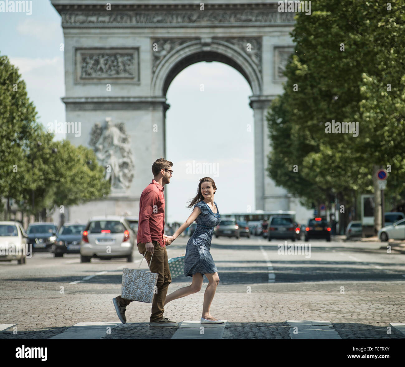 A couple hand in hand carrying shopping bags and crossing the road by a historic monument - Stock Image