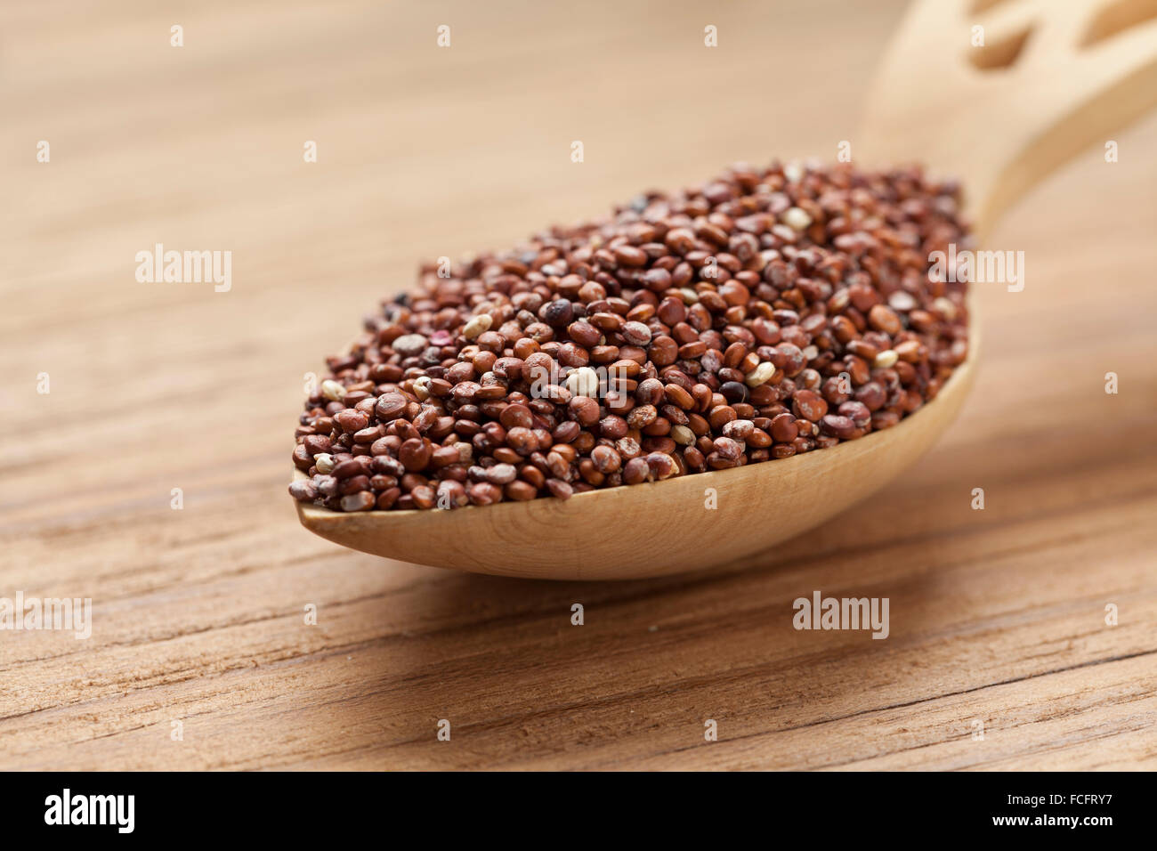 Red raw Quinoa seeds on a wooden spoon - Stock Image