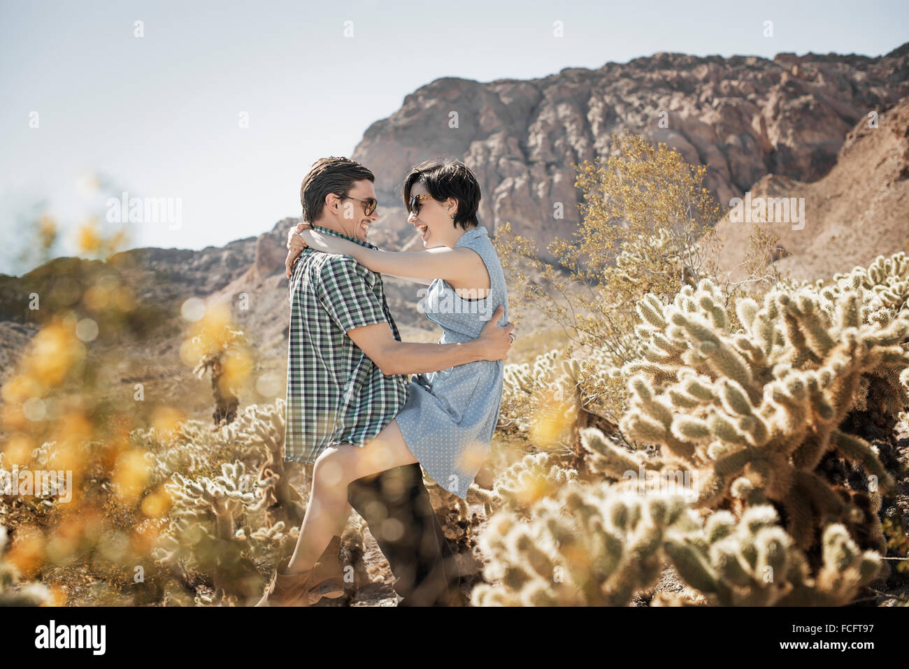 A young couple, man and woman in a desert landscape. - Stock Image
