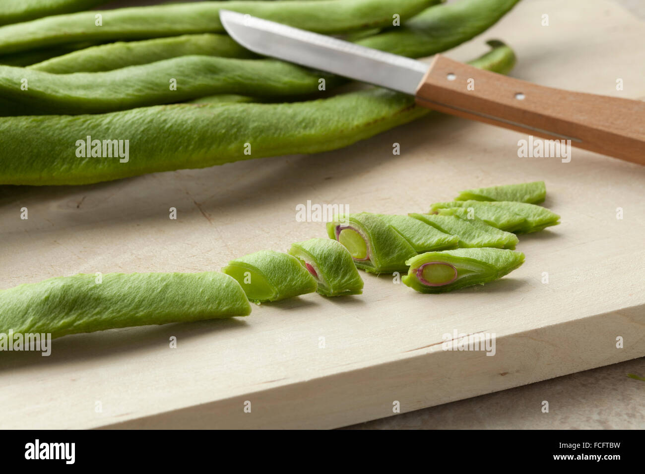 Fresh cut runner beans on a cutting board - Stock Image