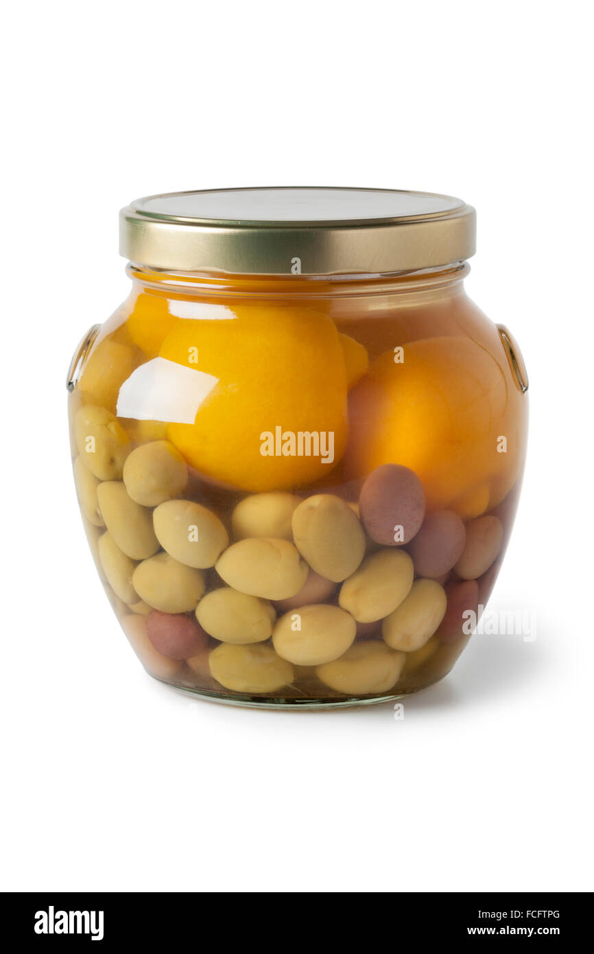 Moroccan glass jar with preserved olives and lemons on white background - Stock Image