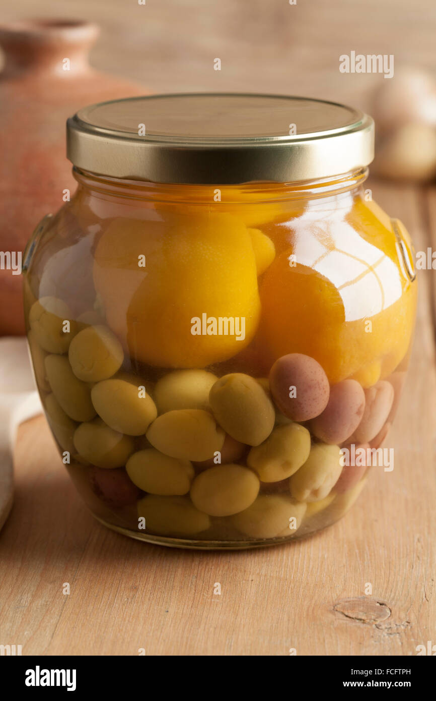 Moroccan glass jar with preserved olives and lemons - Stock Image