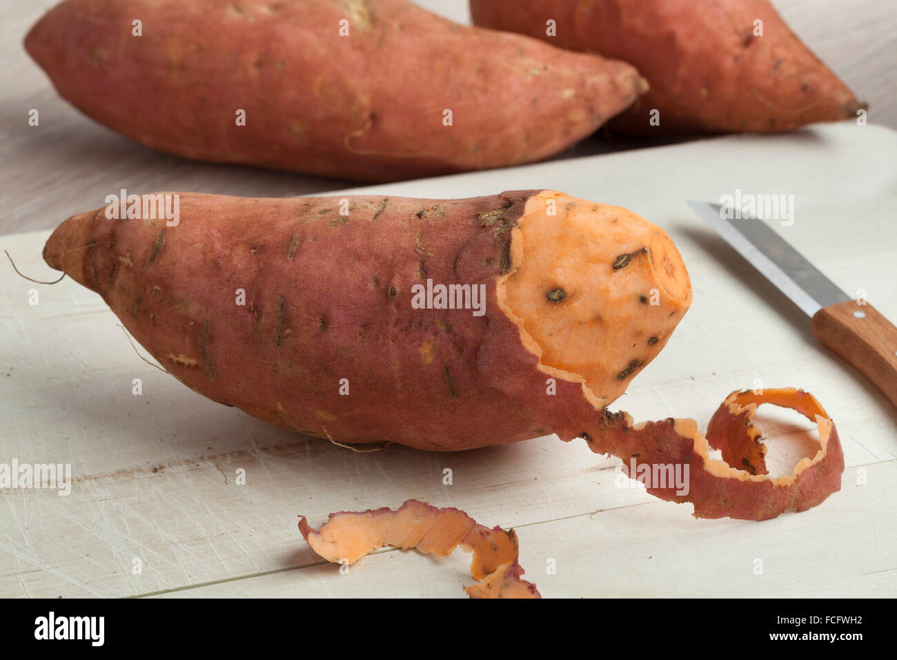 Partially peeled fresh sweet potato - Stock Image
