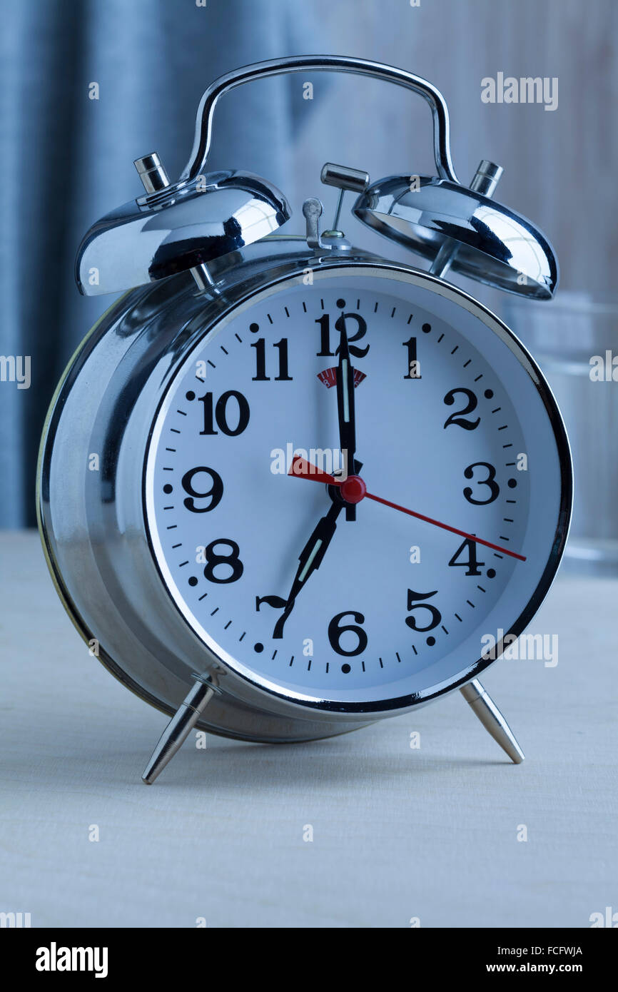 Traditional alarm clock at seven o'clock in the morning - Stock Image