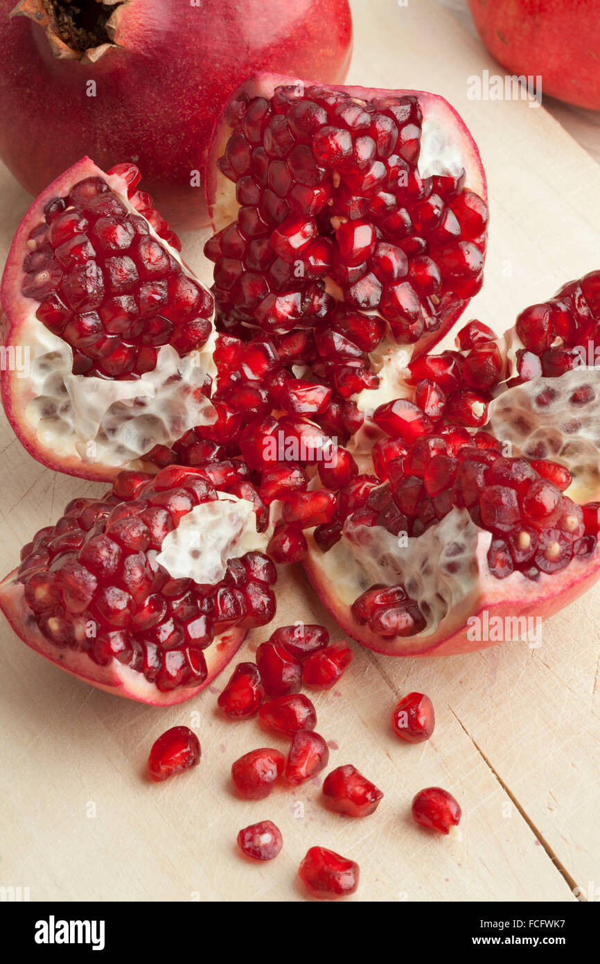 Open fresh red ripe pomegranate fruit and seeds close up - Stock Image