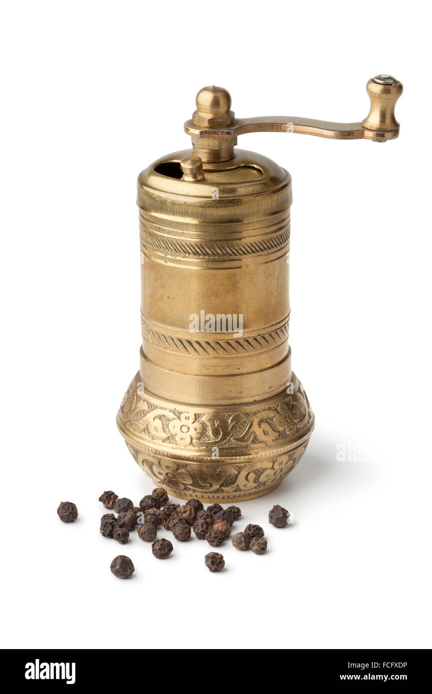 Traditional oriental bronze pepper mill and black pepper on white background - Stock Image