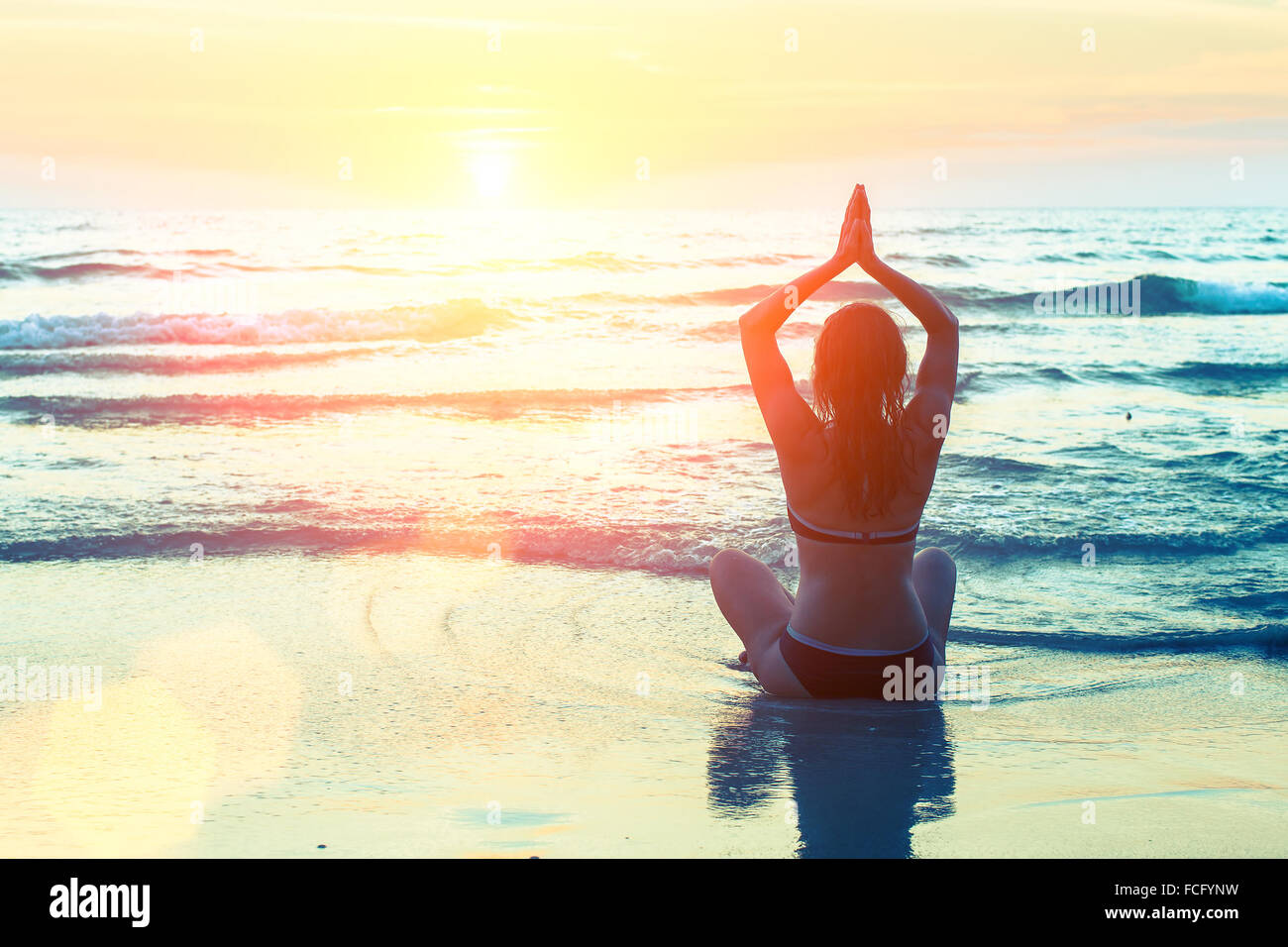 Silhouette of a beautiful yoga woman at sunset in surreal colors. - Stock Image