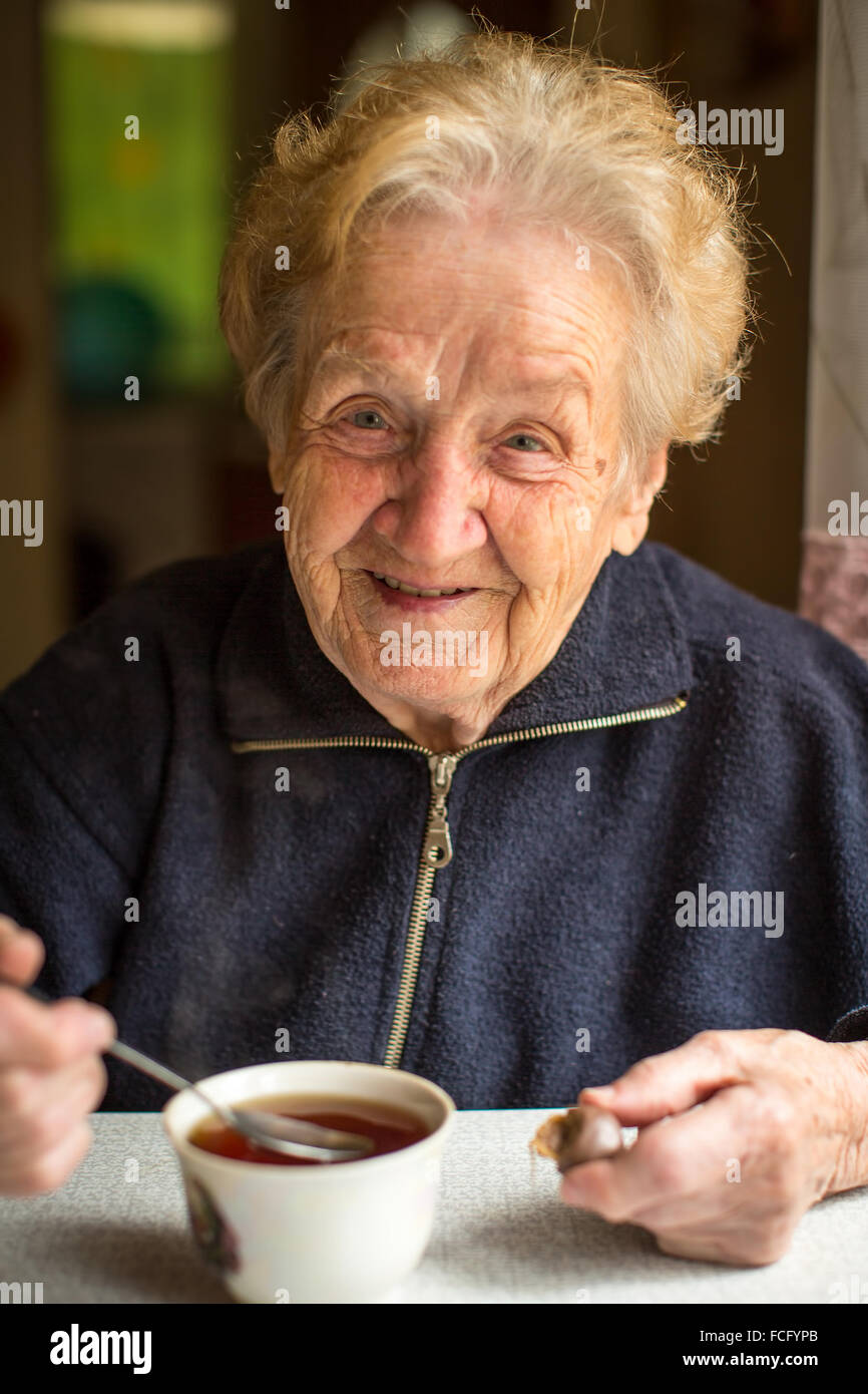 Elderly woman drinking tea in the kitchen. - Stock Image