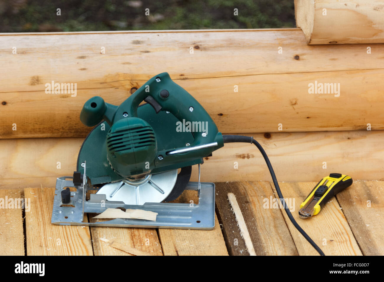 electric circular saw and a knife on a wooden platform Stock Photo