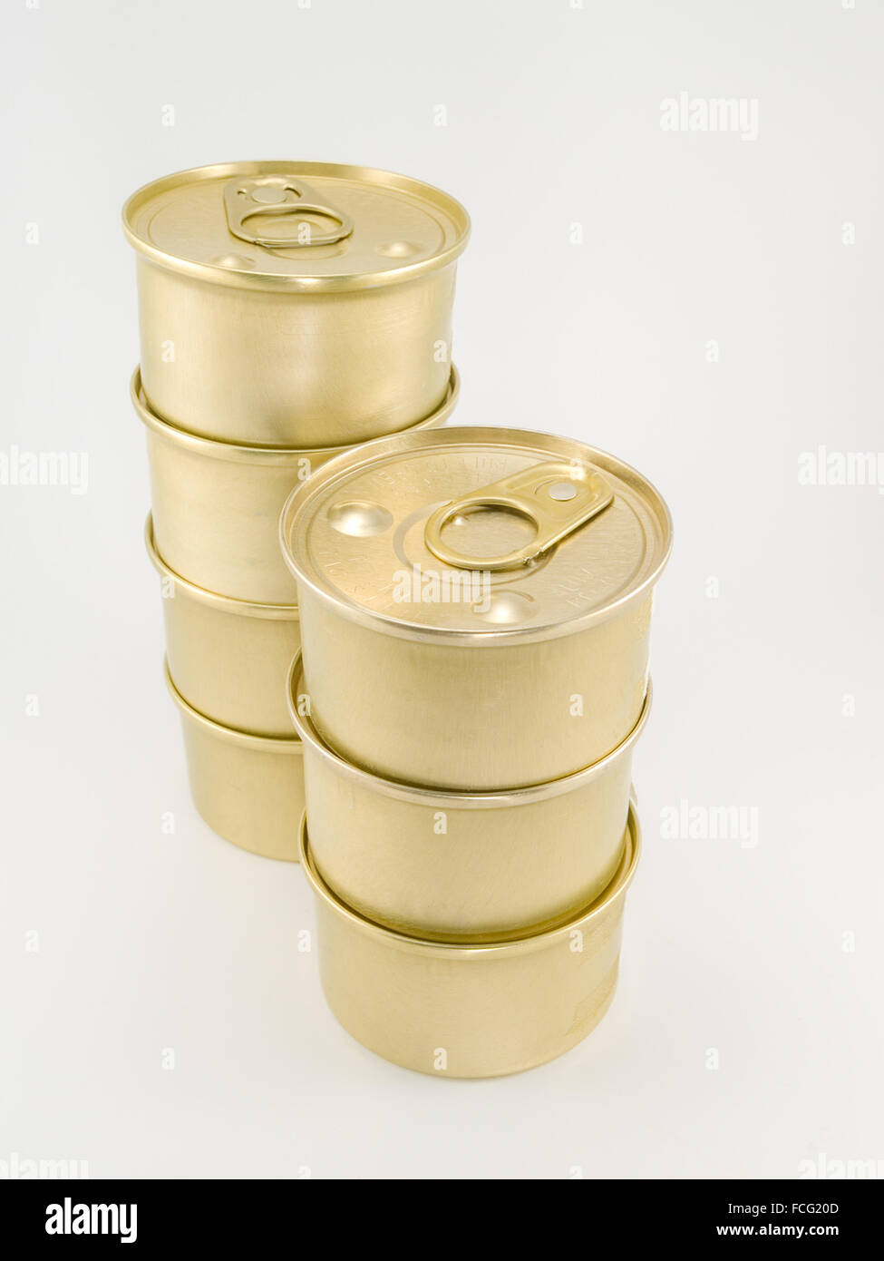 Seven gold blank cat food cans with pull tab piled on top of each other against a white background. - Stock Image