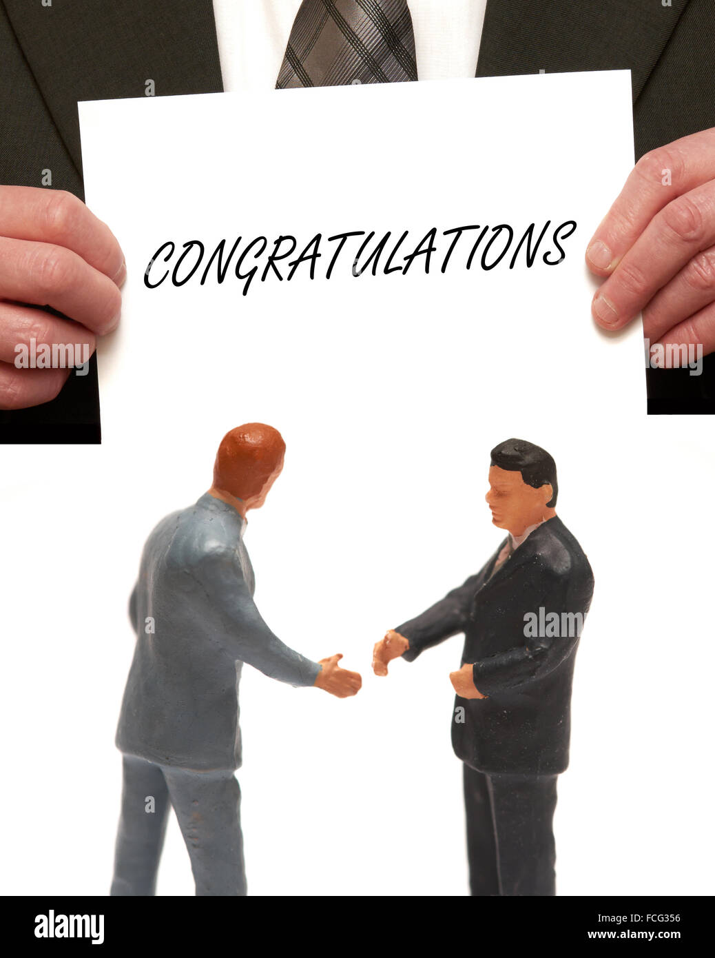 Congratulations concept 2 miniature figurines in suits shaking hands - Stock Image
