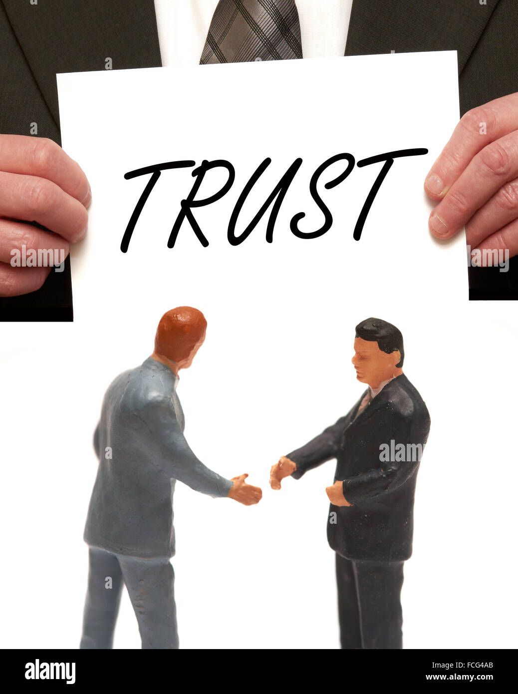 Trust concept  2 miniature figurines in suits shaking hands - Stock Image