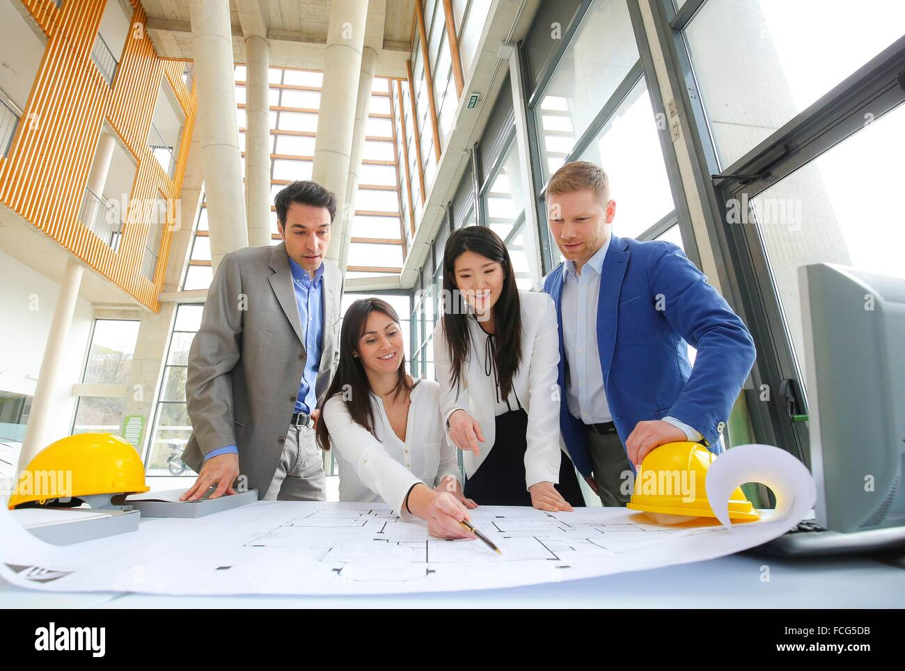 Architects looking at blueprints - Stock Image